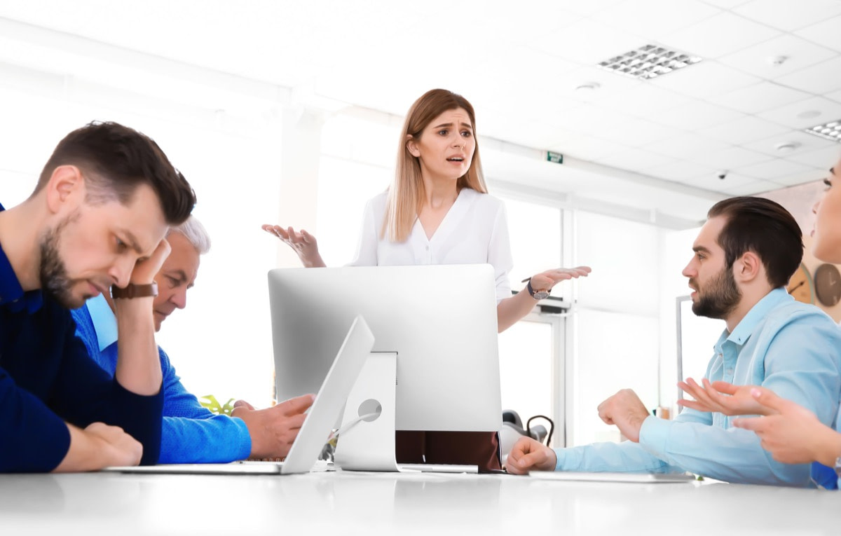Office employees having argument during business meeting; hacktivism concept