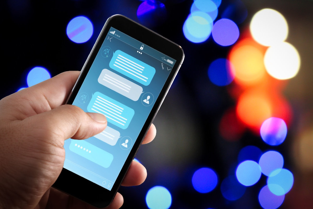 Chatbot conversation with smartphone screen app interface and artificial intelligence technology; uncanny valley concept.