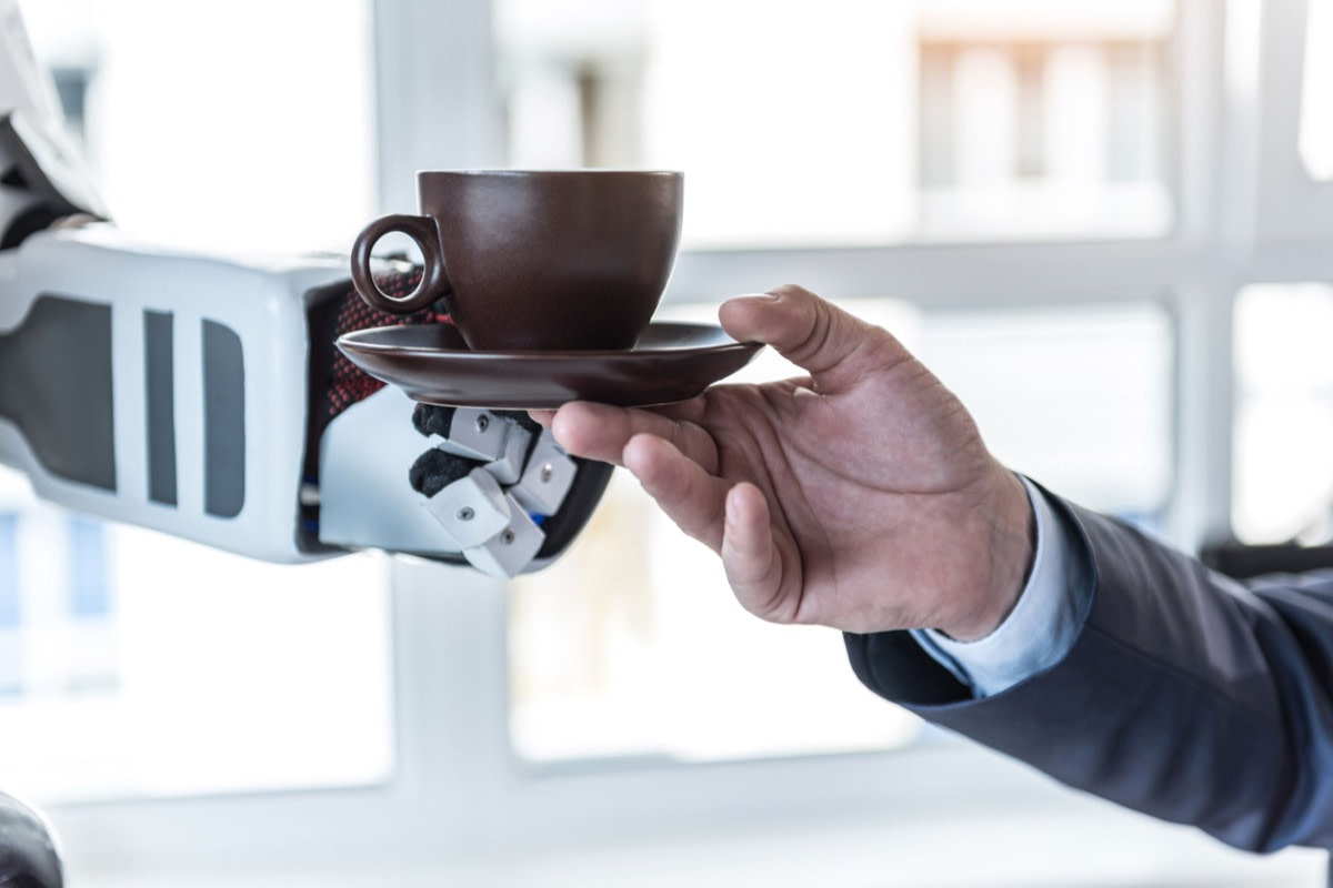 Close up male hand is taking cup of delicious espresso from robot in office; uncanny valley concept
