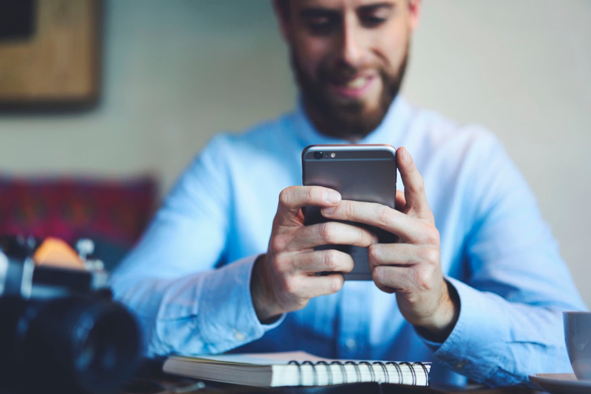 Young smiling bearded male photographer playing online games using modern smartphone connected to 5G wireless internet completing levels