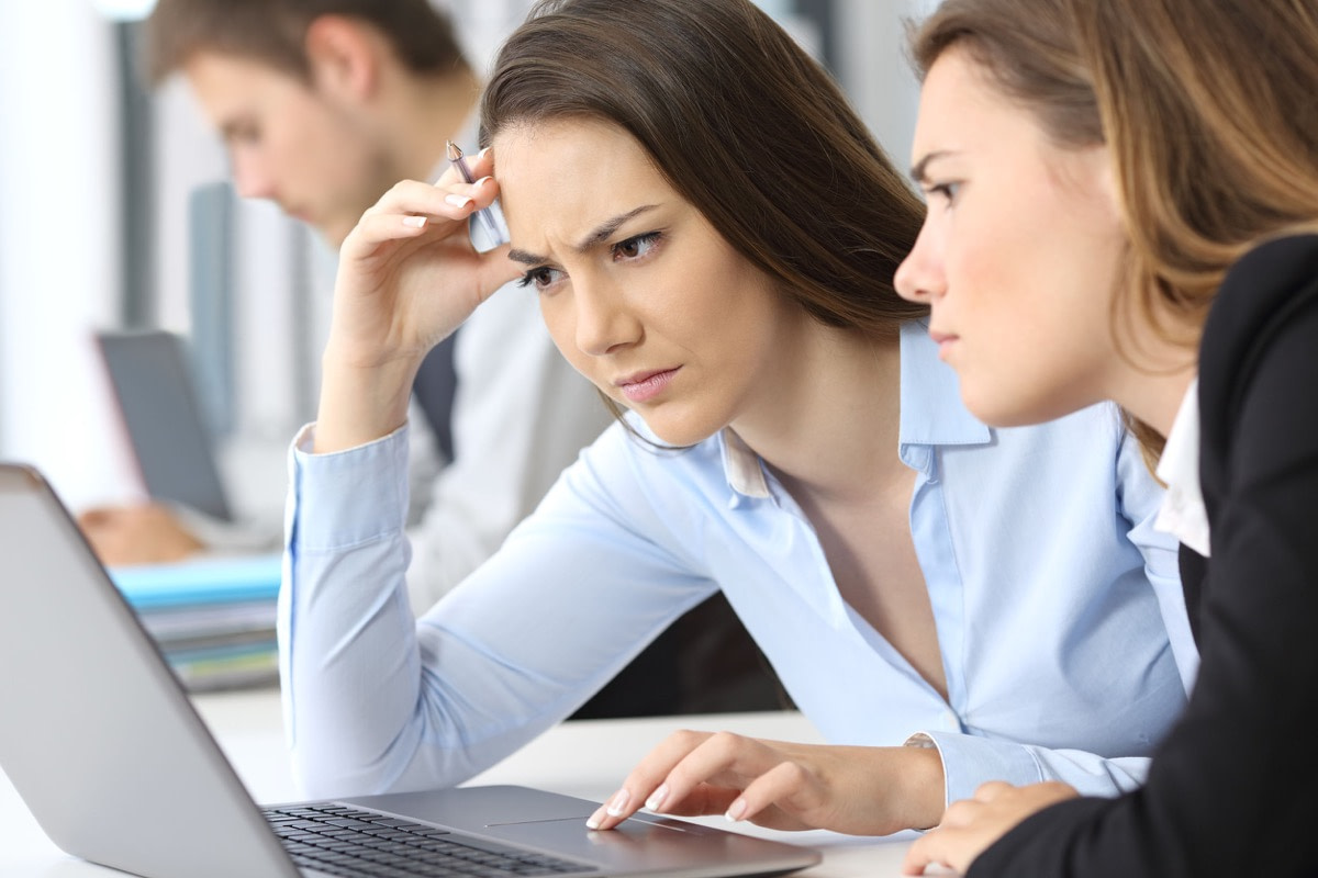 Two worried businesswomen working on line with a laptop at office; Far Right Clickbait concept