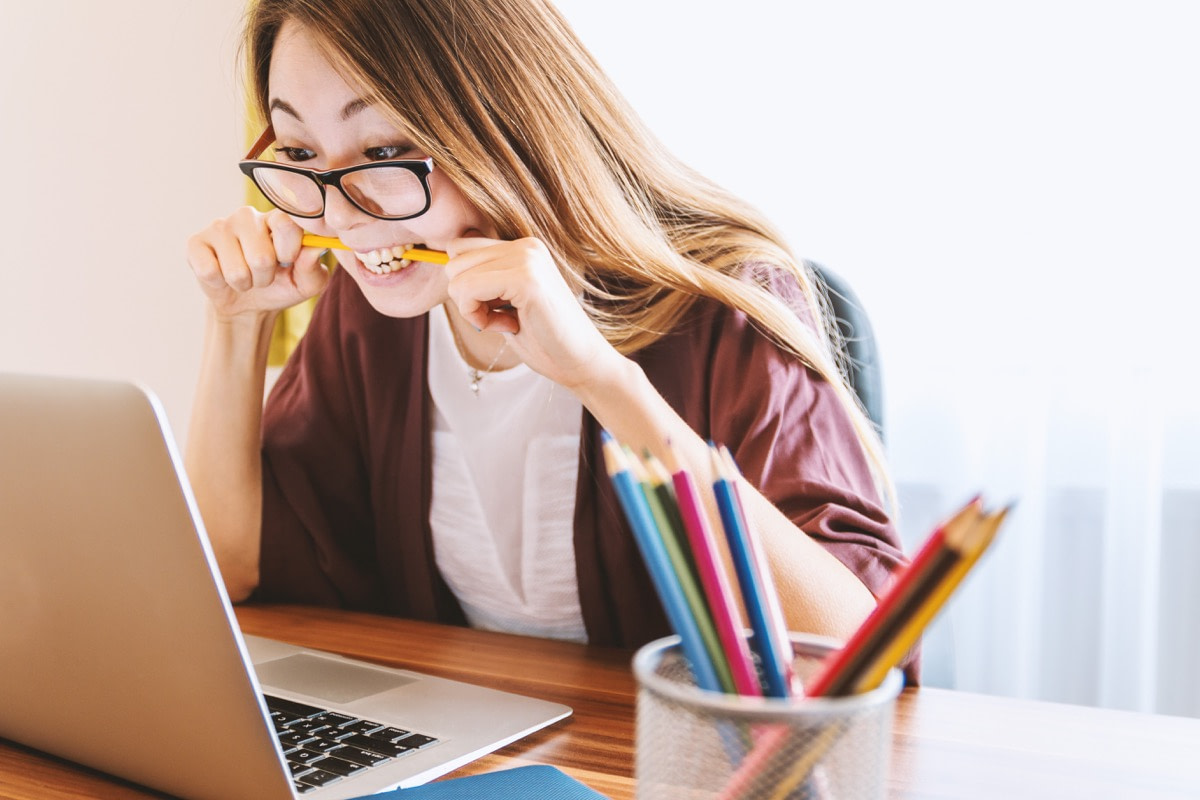 frustrated woman glares at laptop, bites pencil; bad analytics concept