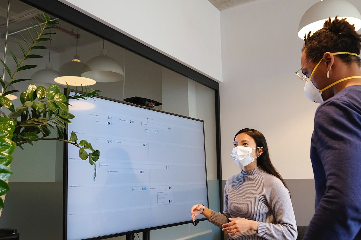 workers presenting at a digital whiteboard; concept: top SaaS Conferences 2021
