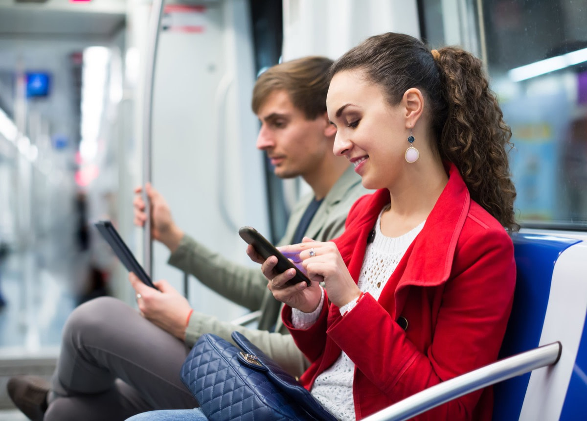 Happy couple reading smartphone and e-book in metro car; trust concept