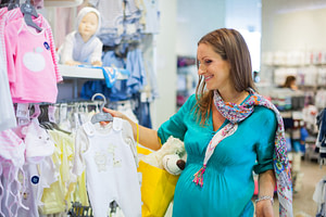 young pregnant woman choosing newborn clothes at baby shop store