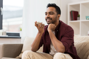 technology, communication and people concept - happy smiling man using voice command recorder on smartphone at home