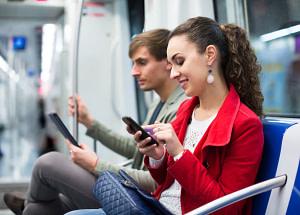 Happy couple reading smartphone and e-book in metro car